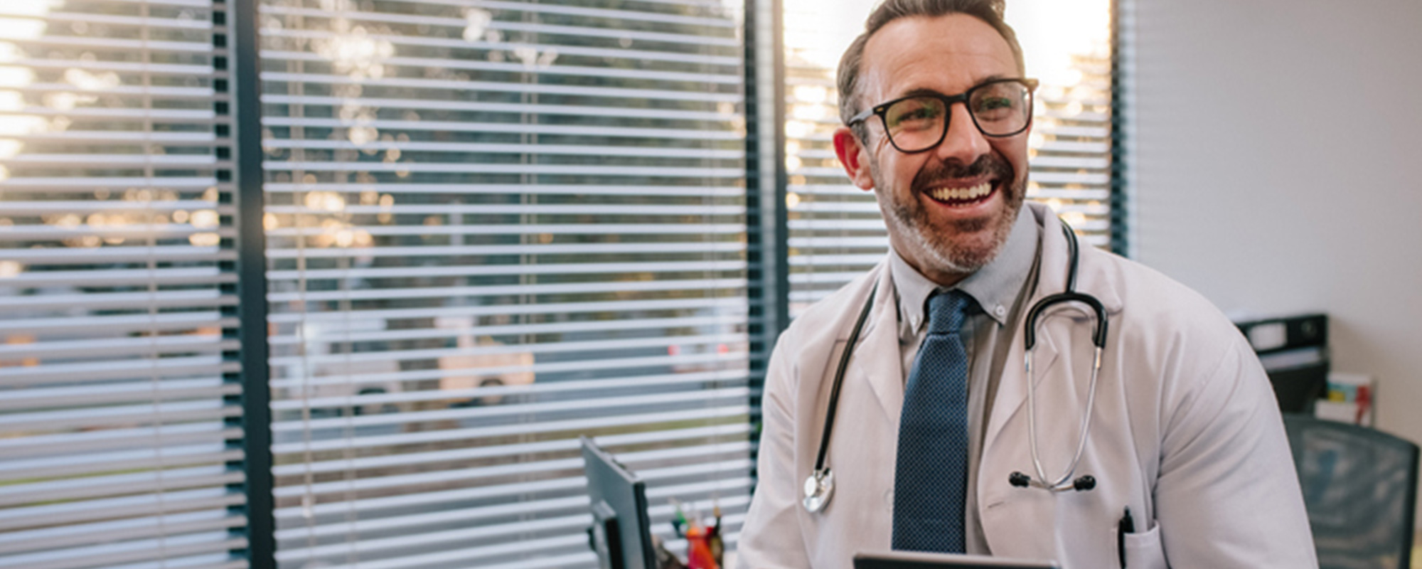 Male doctor smiling in office holding an ipad